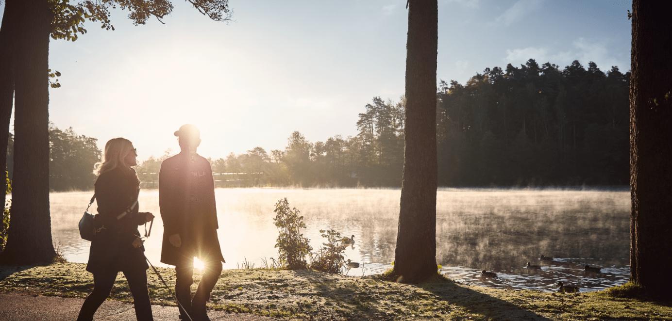 Bild på två personer som går vid en sjö