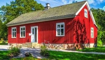 Ett stort rött hus som kan ha solceller på taket