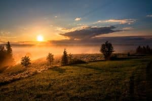 Solnedgång vid horisonten som speglar solens strålar till att använda vår batterilagring solceller